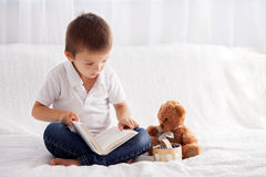 Sweet Little Boy, Reading A Book In Bed And Eating Blueberries, Stock Photo