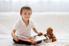 Sweet little boy, reading a book in bed and eating blueberries, Royalty Free Stock Images