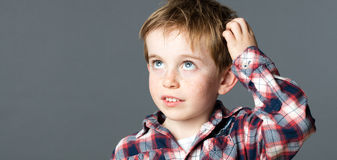 Sweet little boy scratching his head for imagination Stock Images