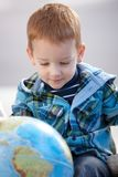 Sweet little boy studying globe at home smiling Stock Photo