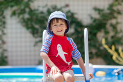 Sweet little boy, swimming in big swimming pool Royalty Free Stock Photography