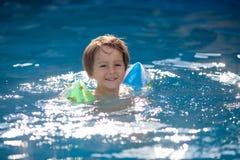 Sweet little boy, swimming in big swimming pool Stock Photo