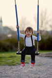 Sweet little boy, swinging in a park Royalty Free Stock Photography