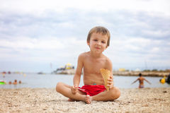 Sweet little child, boy, eating ice cream on the beach Stock Photos