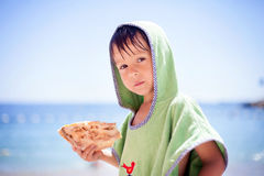 Sweet little child, boy, with green towel, eating pizza on the b Royalty Free Stock Photos
