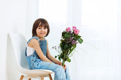 Sweet little child, boy, sitting on a chair at home, holding flo stock photos