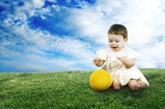 Sweet little child playing with a ball on the lawn Royalty Free Stock Photos