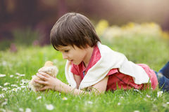 Sweet little child, preschool boy, lying on the grass, playing w Stock Image