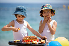 Sweet little children, twin boys, celebrating their sixth birthday on the beach. Cake, balloons, candles, cookies. Childhood happiness concept royalty free stock photo