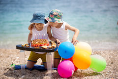 Sweet little children, twin boys, celebrating their sixth birthday on the beach. Cake, balloons, candles, cookies. Childhood happiness concept stock image