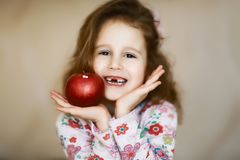 A sweet little curly toothless girl smiles and holds in her hands a red apple, a portrait of a happy child who has lost milk teeth royalty free stock photography