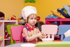 Sweet little cute child kitchener learning to cook. Humorous pho. To Stock Photos