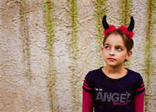 Sweet little devil. Little girl dressed like a devil with a headband with horns Stock Images