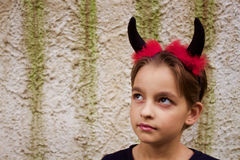 Sweet little devil. Little girl dressed like a devil with a headband with horns Royalty Free Stock Image