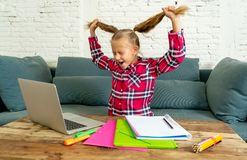 Sweet little elementary school girl pulling her blonde hair in stress getting crazy while trying to study and doing homework at stock image
