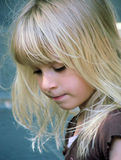 Sweet Little Girl. Portrait of adorable blond female child looking downward with a calm, solemn expression stock images