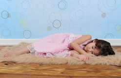 Sweet little girl asleep on furry brown rug Royalty Free Stock Photography