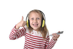 Sweet little girl with blonde hair listening to music with headphones and mobile phone singing and dancing happy Stock Photos
