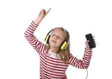 Sweet little girl with blonde hair listening to music with headphones and mobile phone singing and dancing happy Royalty Free Stock Image