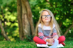 Sweet little girl with a book in the park Royalty Free Stock Photos