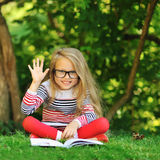 Sweet little girl with a book showing five - outdoors Stock Photography