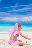 Sweet little girl with butterfly wings on white beach Royalty Free Stock Images