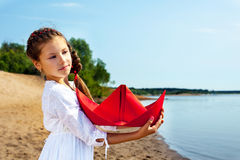 Sweet little girl cuddles paper boat Stock Photography