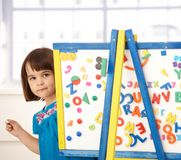 Sweet little girl at drawing board Royalty Free Stock Photos