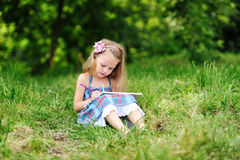 Sweet little girl drawing in a park Stock Image