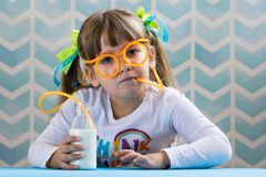 Sweet little girl drinking milk with funny glasses straw. royalty free stock image