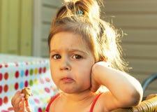 Sweet little girl eating cake at sunset Royalty Free Stock Image