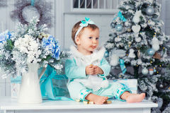 A sweet little girl is eating a chocolate candy. Christmas mood. Stock Image