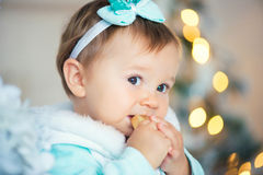 A sweet little girl is eating a chocolate candy. Christmas mood. Stock Photography