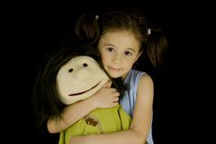 Sweet little girl embraces her favorite doll Stock Photo