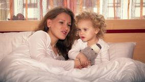 Sweet little girl and her beautiful young mom singing lullaby for toy bear stock video