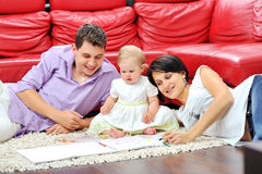 Sweet little girl with her parents drawing and having fun Royalty Free Stock Photo