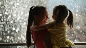 Sweet Little Girl is Hugging and Kissing Her Beautiful Young Mom. Happy Mothers Day. Waterfall is on Background.