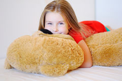 Sweet little girl is hugging a teddy bear while lying in her bed Royalty Free Stock Photography