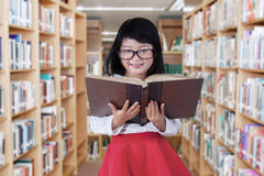 Sweet little girl in the library. Lovely elementary school student standing in the library while reading a textbook Stock Photos