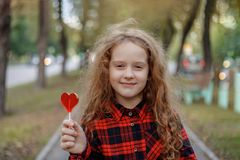 Sweet girl with a lollipop in a autumn park. Royalty Free Stock Images