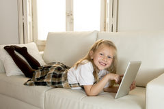 Sweet little girl lying on home sofa couch using internet app on digital tablet pad Royalty Free Stock Photo