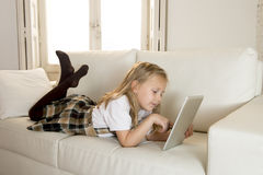 Sweet little girl lying on home sofa couch using internet app on digital tablet pad Royalty Free Stock Photos