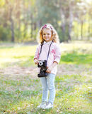 Sweet little girl with old vintage retro camera outdoors Stock Photography