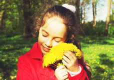 Sweet little girl outdoors with dandelions. Toned Royalty Free Stock Photography