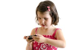 Sweet little girl in pink dress play on smartphone concetrated i Royalty Free Stock Photos