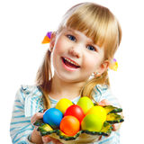 Sweet little girl with plate of Easter eggs. Portrait of smily young girl with Easter eggs Stock Photo