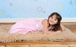 Sweet little girl playfully posing on furry rug Stock Image
