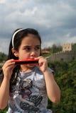 Sweet little girl playing mouth harmonica Stock Image