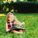 Sweet little girl reading book in a summer park Royalty Free Stock Photo