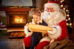 Sweet little girl in Santa Claus lap choosing her present. Sweet little girl in Santa Claus lap undecided choosing her present from list, childhood in Christmas Stock Image